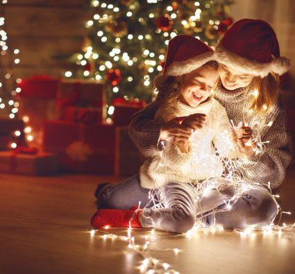 mother holds daughter while both gleefully look down at a string of christmas lights that rests upon their laps