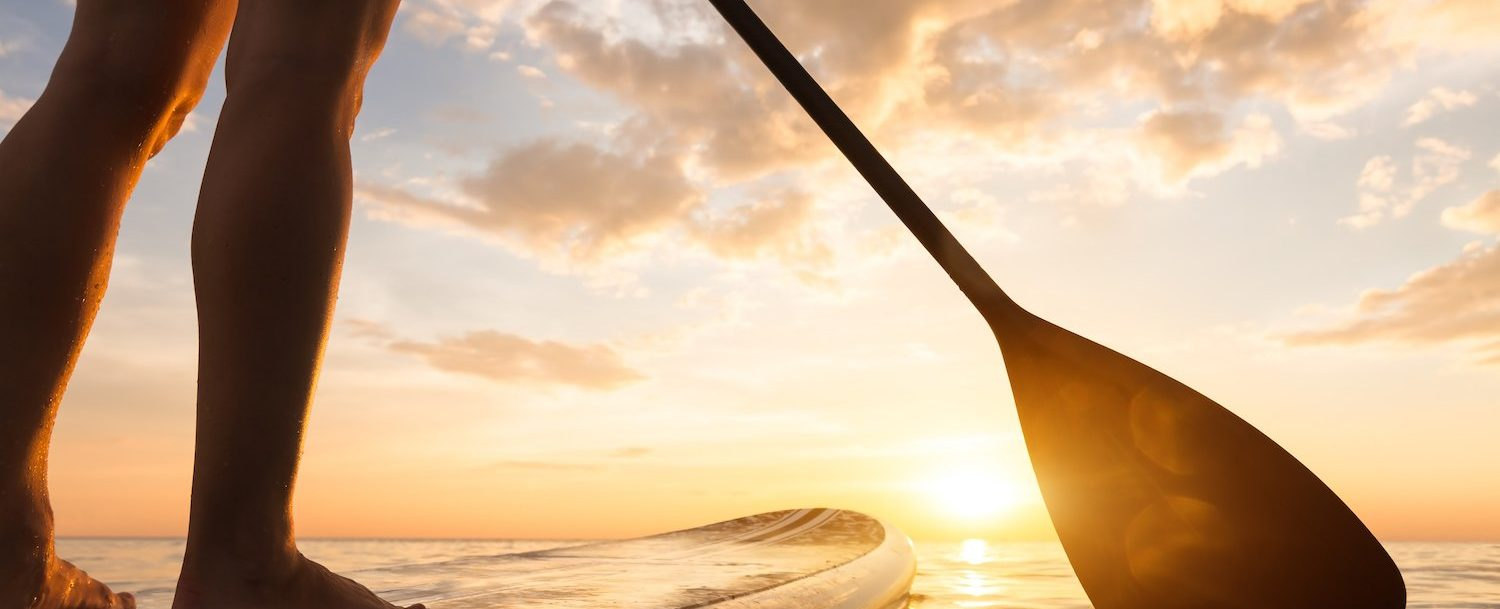 Stand up paddle boarding on a quiet sea with warm summer sunset colors, close-up of legs